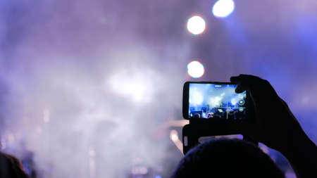 Unrecognizable hand silhouette taking photo or recording video of live music concert with smartphone. Photography, entertainment and technology concept Foto de archivo