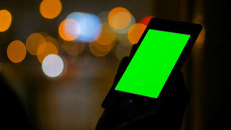 Woman looking at vertical smartphone with green screen at night. Blurred traffic bokeh light. Mock up and technology concept