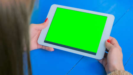Woman looking at horizontal tablet computer with green screen. Close up shot of woman hands with pad. Technology, mockup and internet concept