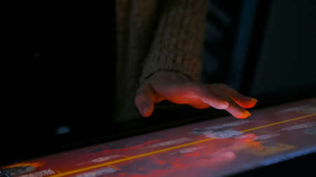 Woman using interactive touchscreen display in modern historical museum. Evening time, lowlight. Education and entertainment concept. Close up shot Foto de archivo