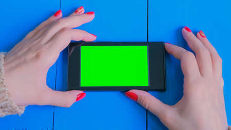 Woman looking at horizontal smartphone with green screen. Close up shot of woman hands with mobile on blue wooden table. Technology, mockup and internet concept Foto de archivo