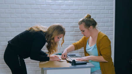 Two professional women decorators, designers working with kraft paper and using paper cutter, guillotine at workshop, studio. Crafting work, decoration and art concept