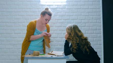 Professional woman decorator, designer explaining how to make envelope for assistant. Design, handmade and art concept