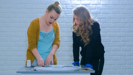 Two professional women decorators, designers painting wooden circle decoration with stencil at workshop, studio. Paint, handmade and art concept