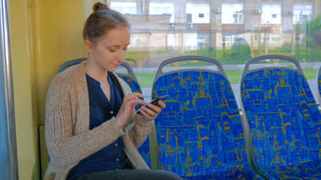 Woman travelling by tram and using smartphone. Travel, transport and technology concept