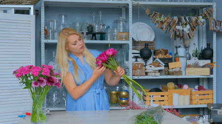 Professional floral artist, florist in blue dress sorting flowers - pink peonies for bouquet at workshop, flower shop. Floristry, handmade and small business concept Foto de archivo