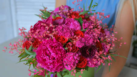 Professional woman floral artist, florist showing beautiful wedding bouquet at workshop, flower shop. Close up shot. Floristry, handmade and small business concept Foto de archivo