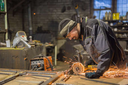 Professional blacksmith sawing metal with hand circular saw at forge, workshop. Handmade, craftsmanship and blacksmithing concept Foto de archivo