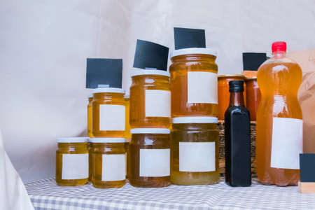 Jars of homemade honey with empty white label at outdoor market. Mock up, copyspace, template and street market concept
