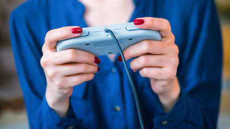Woman using retro gaming console controller. Gaming, hobby, technology and leisure time concept Foto de archivo