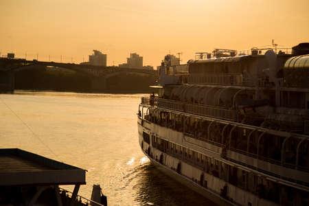 Big passenger ship on river near town at sunset Foto de archivo