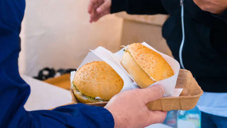 Close up shot of man hands taking burgers at street food festival. Outdoor cooking, gastronomy, takeaway food, people and service concept