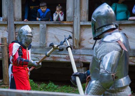 NIZHNIY NOVGOROD, RUSSIA - JUNE 2018: Volga Shtandart Historic Festival. Two militant medieval knights fighting at historical festival. Fantasy, reenactment and medieval culture concept