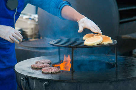 Chef preparing burgers at street food festival. Outdoor cooking, gastronomy and street food concept