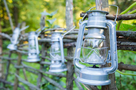 Rustic lanterns hanging on the wooden fence