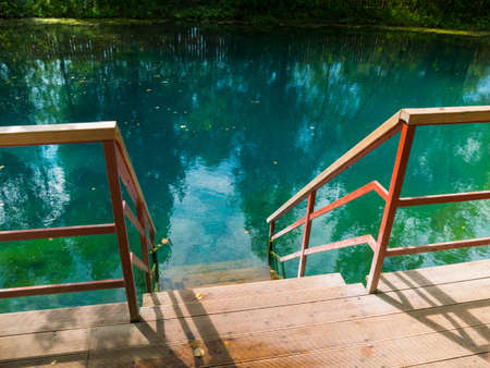 Wood stairway down the turquoise clear water