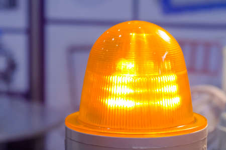 Danger, legal, alert light, attention, hazard, manufacturing concept. Close up of orange alarm lamp signal warning flashing light for industrial machinery at emergency, support and services exhibition