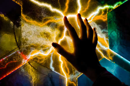 Interactive touchscreen exposition. Woman hand touching colorful plasma panel display in dark room - close up view. Electricity, education, science, futuristic and physics concept