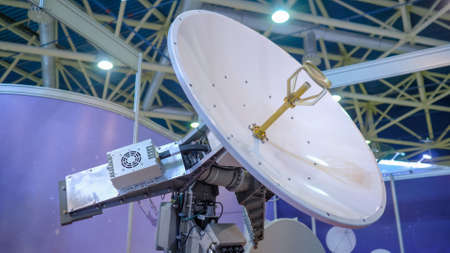 White rotating satellite dish antenna, VSAT parabolic receiver using to receive or transmit information at telecommunication exhibition. Broadcasting, communication, technology concept 스톡 콘텐츠