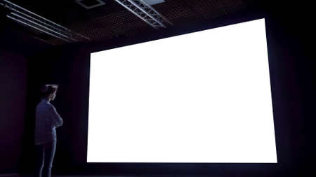 Mock up, white screen, futuristic, template, education concept. Woman looking at large wall blank interactive white display in dark room of modern technology exhibition or museum. 免版税图像