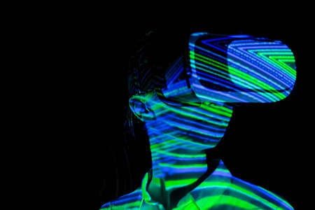 Woman using virtual reality headset and looking around at interactive technology exhibition with colorful projector light illumination. VR, augmented reality, immersive, entertainment concept