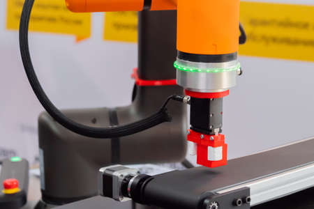 Pick and place robotic clamp arm manipulator moving red toy blocks at modern robot trade show, exhibition - close up view. Manufacturing, engineering, industrial, ai, automated technology concept