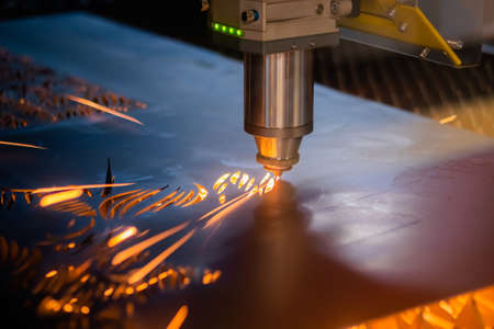 Automatic cnc laser cutting machine working with sheet metal with sparks at factory, plant. Metalworking, industrial, machining, technology, manufacturing, equipment concept