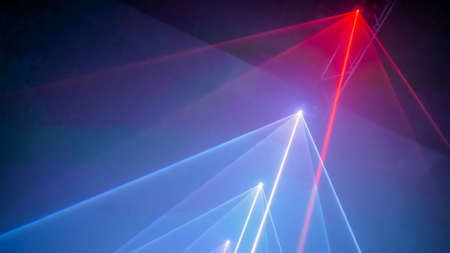 Interactive exposition in modern science museum or exhibition: bright laser show installation with color rays or beams in dark room. Performance, technology, visuals, digital, contemporary art concept Stock Photo