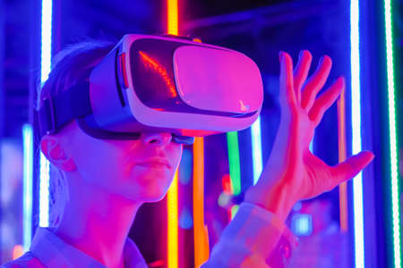 Woman using virtual reality headset and moving hand at interactive technology exhibition with colorful illumination: close up. VR, futuristic, retrowave, immersive, entertainment concept