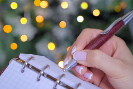 Woman writing to do list in vintage notebook organizer - close up view. Garland light illumination bokeh background. Christmas, motivation, management, productivity, planning, reminder, goals concept