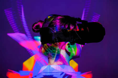 Woman using virtual reality headset, looking right at interactive technology exhibition with multicolor projector light illumination. VR, augmented reality, immersive, entertainment concept