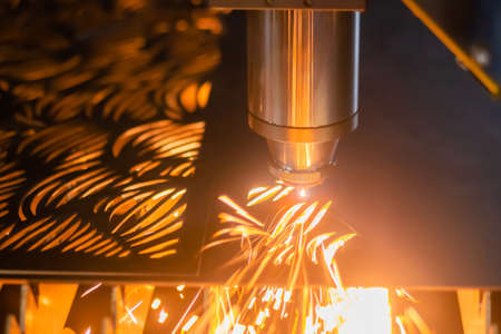 Laser cutting machine working with sheet metal with sparks at factory, plant: close up. Metalworking, industrial, equipment, technology, machining, manufacturing concept