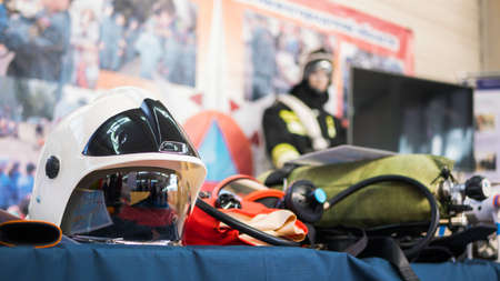 Special equipment of rescue worker - mask, helmet, oxygen cylinder at emergency services show Фото со стока