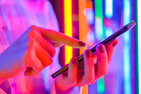 Woman using smartphone device at interactive exhibition or museum with purple illumination - scrolling and touching - close up view. Futuristic, retrowave, immersive, entertainment concept