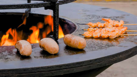 Process of grilling fresh tiger prawns and meat sausages on brazier with hot flame at summer food market - close up. Outdoor cooking, gastronomy, seafood, barbecue, street food concept