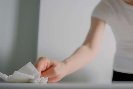 Woman cleaning white dining table with antiseptic disinfectant wet wipe - close up. Disinfection, protection, prevention, housework, COVID-19, coronavirus, sanitation concept
