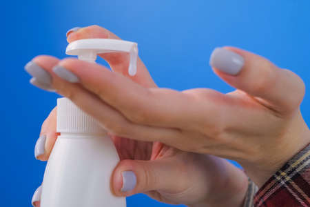 Woman pushing dispenser, squeezing out antiseptic gel on palm, cleaning hands - close up side view. Disinfection, protection, prevention, COVID-19, coronavirus, safety, sanitation concept