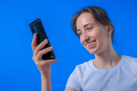 Positive woman in white shirt smiling, using smartphone, having video chat, job interview, distant consultation in room with blue wall. Communication, lifestyle, conference, online technology concept Фото со стока