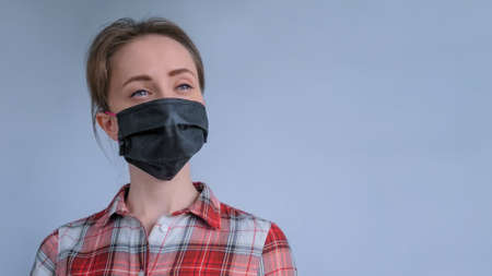 Portrait of woman wearing black medical face mask, red plaid shirt, looking away in room with grey wall at home. Self isolation, prevention, quarantine, COVID19, copyspace, coronavirus, safety concept