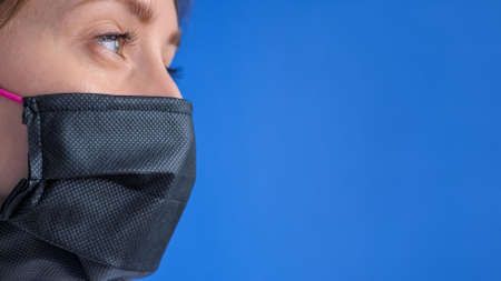 Portrait of woman wearing black medical face mask, looking away against blue background in room at home. Self isolation, prevention, quarantine, COVID19, coronavirus, safety, copy space concept