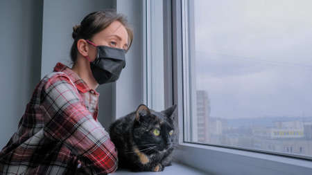 Portrait of pensive woman in medical face mask, red plaid shirt and black cat looking out of window in grey room at home. Self isolation, prevention, quarantine, COVID 19, coronavirus, safety concept