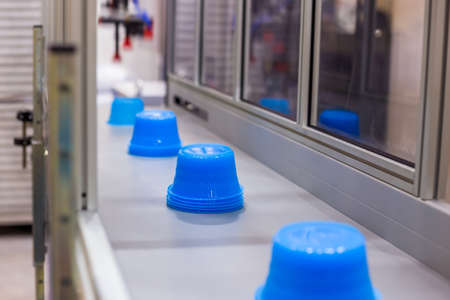 Moving polypropylene pots on conveyor belt of automatic plastic injection molding machine at exhibition, trade show. Manufacturing, industry and automated technology equipment concept