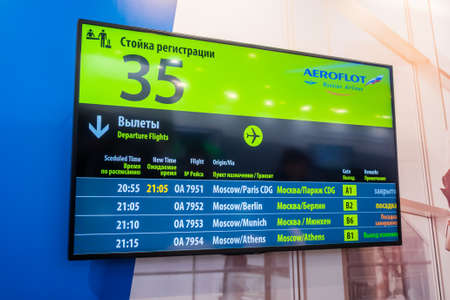 MOSCOW, RUSSIA - JUNE 01, 2019: Aviation exhibition. Russian airport travel information departure board on wall at air transport trade show Редакционное