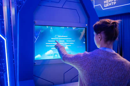 MOSCOW, RUSSIA - JUNE 05, 2019: Technology exhibition. Woman using interactive touchscreen display of electronic informational wall kiosk at modern sci-fi museum. Education, futuristic concept