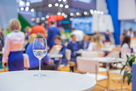 Close up view: glass of water, champagne or wine on white table against blurred business meeting, conference, seminar background. Corporate and communication concept Фото со стока