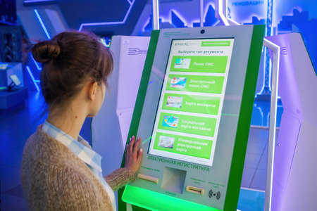 MOSCOW, RUSSIA - JUNE 05, 2019: Technology exhibition. Woman using interactive touchscreen display of electronic document informational kiosk at museum. Education, futuristic, technology concept
