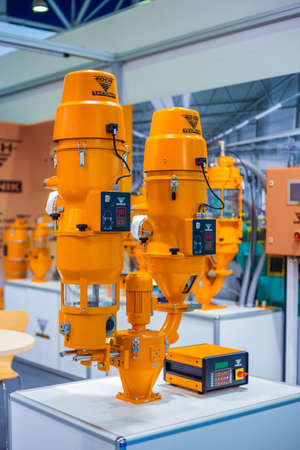 MOSCOW, RUSSIA - JUNE 05, 2019: Plastic exhibition. Orange gravimetric dosing mixing system - Koch technik at trade show. Technology, production, manufacturing, industrial, automatic equipment concept