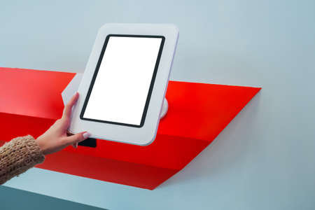 Woman looking at blank vertical interactive touchscreen white display of electronic tablet kiosk at futuristic exhibition. White screen, mock up, future, copyspace, template, technology concept