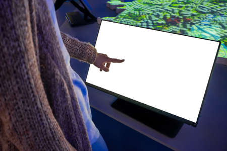 Woman hand using white blank interactive touchscreen display of electronic multimedia kiosk in dark room - scroll, touch - close up. Mock up, copyspace, template and technology concept Фото со стока