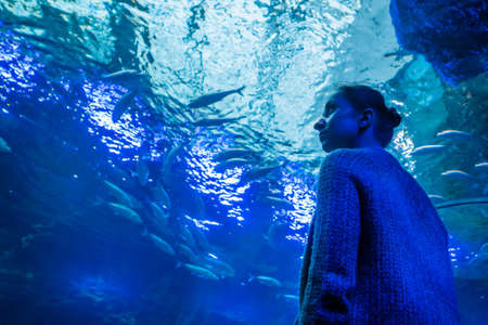 Underwater life, tourism, education and entertainment concept. Portrait of woman looking at fish vortex in large public aquarium tank at Oceanarium with blue low light illumination - low angle view